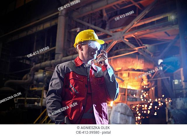 Steelworker talking, using walkie-talkie in steel mill