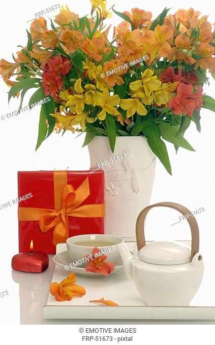 Arrangement of tea pot, a cup of tea, gift an bouquet