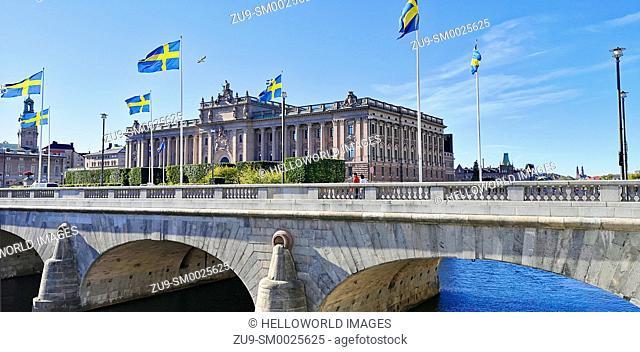 Swedish flags flying on Norrbro Bridge (North Bridge) in front of the Parliament House (Riksdagshuset), Stockholm, Sweden, Scandinavia