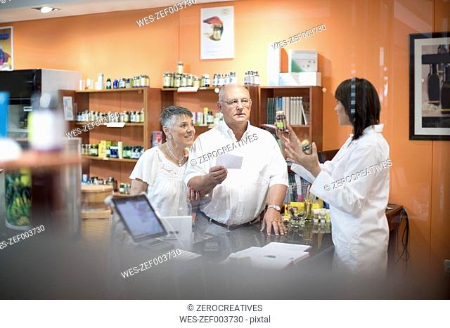 Female health shop pharmacist advising senior couple