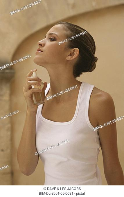 Young woman applying perfume to her neck