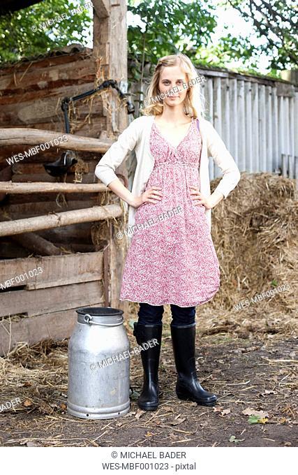 Germany, Saxony, Young woman with milk churn, portrait