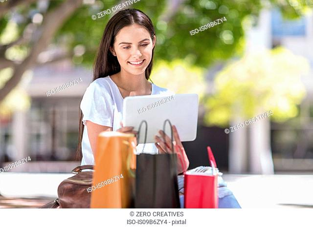 Young woman sitting outdoors, using digital tablet, shopping bags beside her
