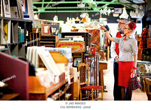 Quirky vintage couple shopping together in antiques emporium