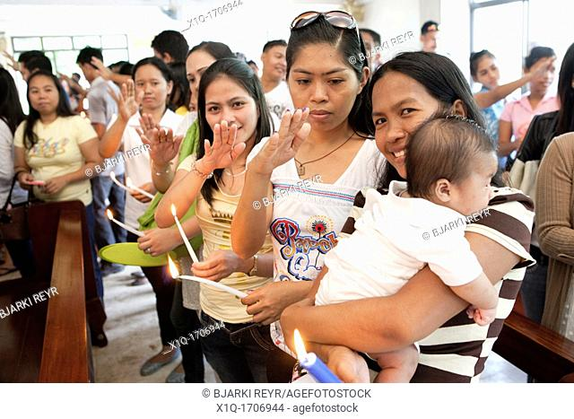 Lapu-Lapu City, Philippines, 26/02/2012: 200-300 babies being baptised in a single 3 hour ceremony at Mactan Air Base Chapel
