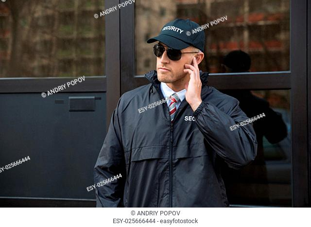 Young Security Guard Standing In Front Of The Glass Door Entrance