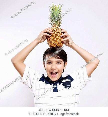 Portrait of a boy carrying a pineapple on his head