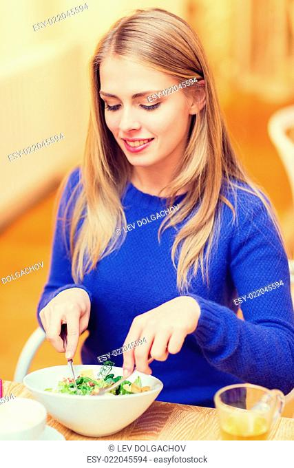 people, leisure, eating and food concept - happy young woman having dinner at restaurant, cafe or home
