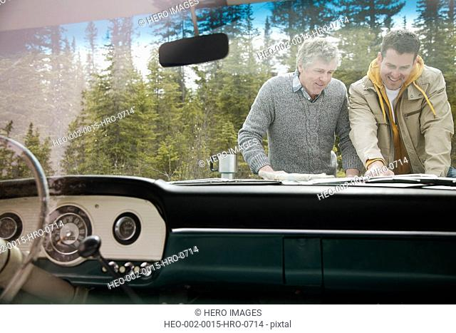 father and son reviewing map on hood of truck