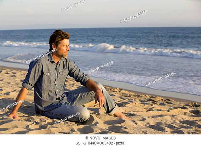 Contemplative Mid-Adult Man Sitting on Sandy Beach