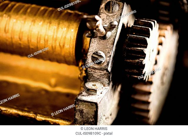Close up of gold ink on printing machinery in printing press workshop