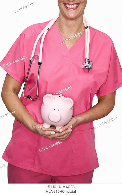 Close-up of a female nurse holding a piggy bank