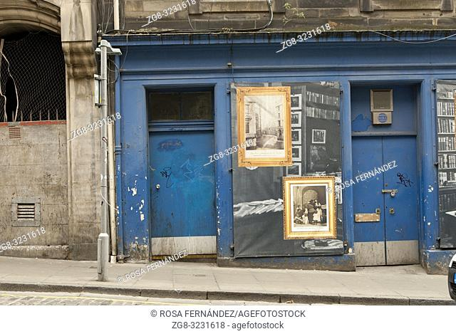 Facade of an abandoned shop with blue doors and old pictures of families, streets and librairies, Victoria Street, Edinburgh, Scotland, United Kingdom