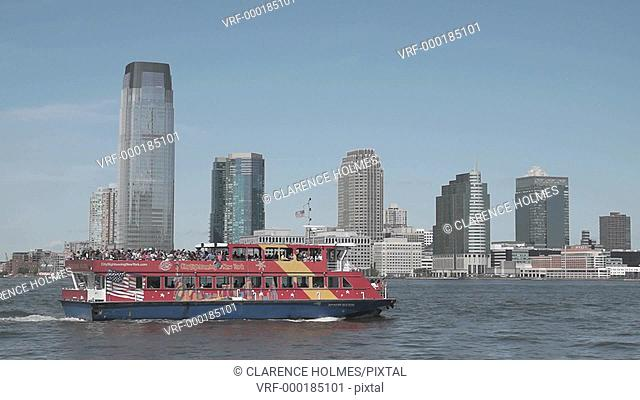 A City Sightseeing New York tour boat heads north on the Hudson River with a load of tourists in front of the skyline of Jersey City, New Jersey