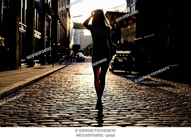 USA, New York, Brooklyn, Dumbo, silhouette of young woman standing on street at backlight