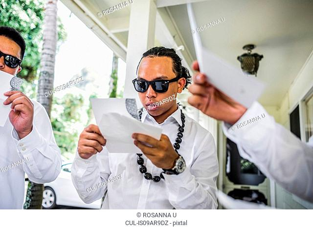 Young men preparing for Hawaiian wedding wearing kukui nut beads, Kaaawa, Oahu, Hawaii, USA