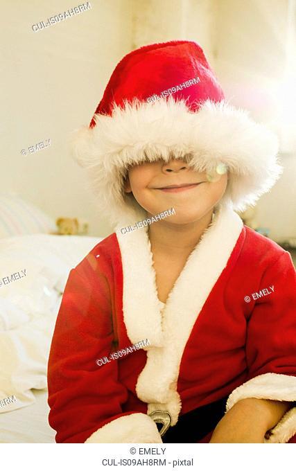 Portrait of young boy hidden by santa outfit cap