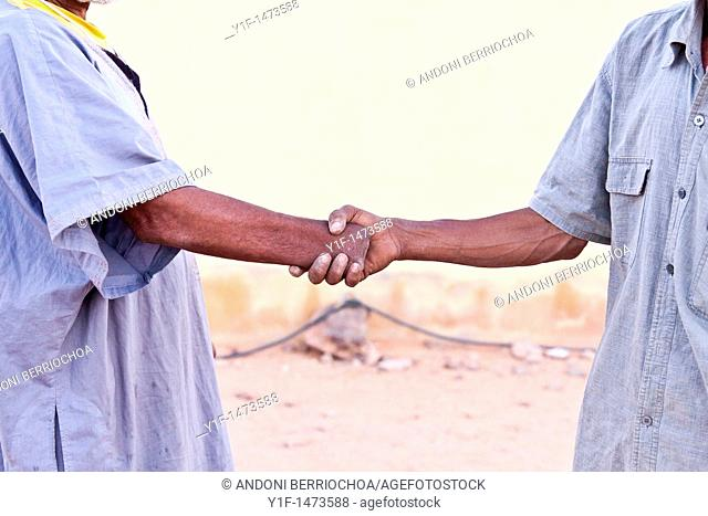 Patient in the Shreif Martyr hospital for war victims, in the Saharawi refugee camps in Tindouf,  Algeria, shakes hands with the hospital guard