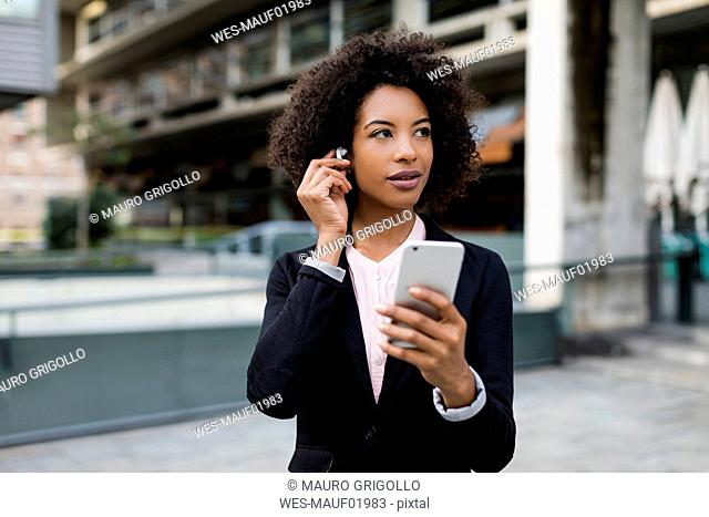 Portrait of businesswoman with smartphone putting on earphones