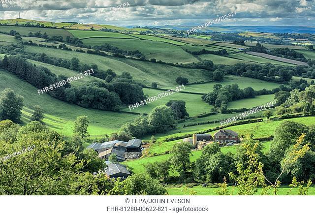 View across farmland and farm buildings, near Dolfor, Newtown, Powys, Wales, July