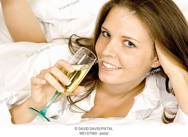 Caucasian woman in early 20's laying in bed with a glass of White Wine