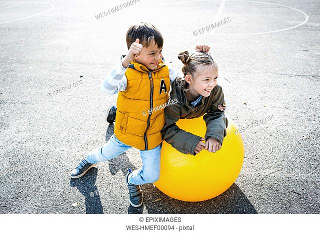 Two children having fun with gym ball
