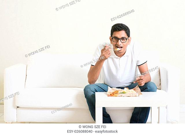 Lonely young single Indian man eating food alone, copy space at side. Having nasi lemak as lunch. Lifestyle of Asian guy at home