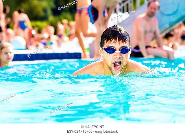 Man with goggles swimmning in the pool. Summer heat and water