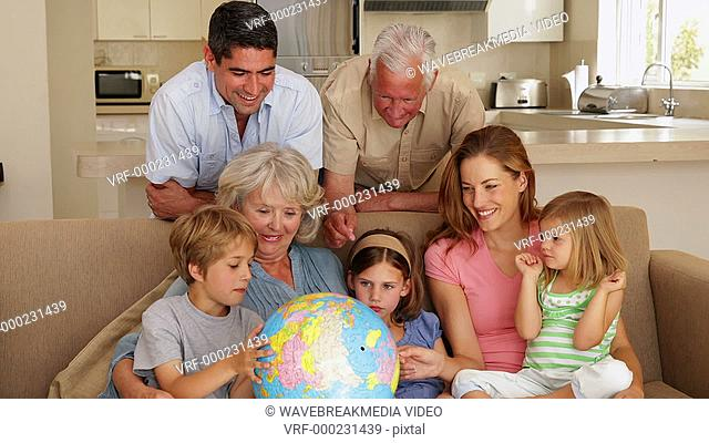 Extended family looking at globe together on couch at home in the living room