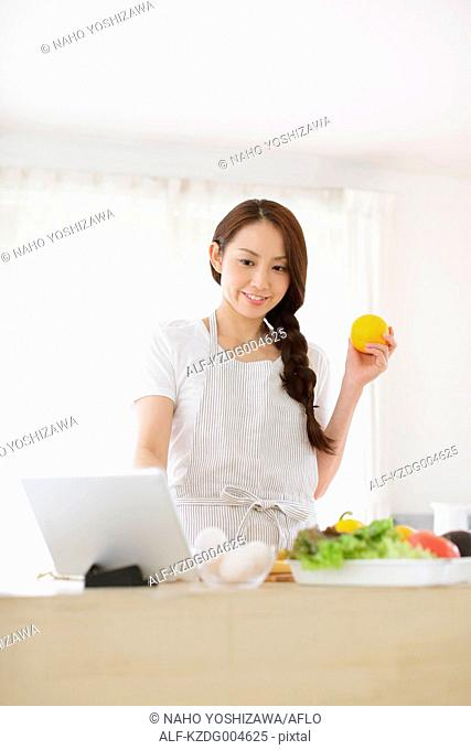 Young attractive Japanese woman cooking at home with tablet