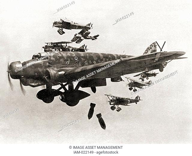A Savoia-Marchetti SM.81 during a bombing raid. The black crosses distinctives in the tails are Saint Andrew's Cross, the insignia of the Spanish Nationalist...