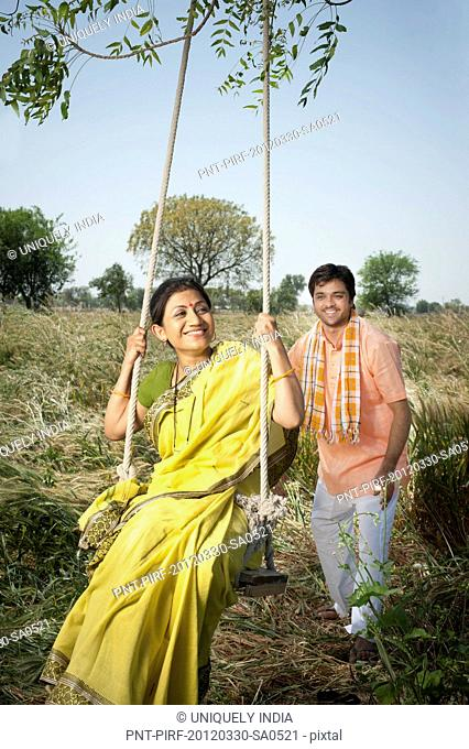 Farmer pushing his wife on a swing in the field, Sohna, Haryana, India