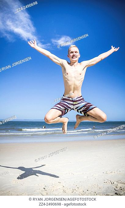 Action picture of happy man star jumping on the Australia beach location. Taken Bribie Island, Queensland