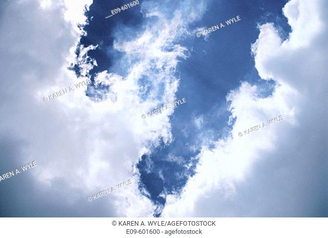 Clouds with sunlit rims and dark blue sky