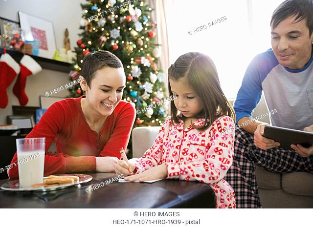 Parents helping girl write letter to Santa Claus