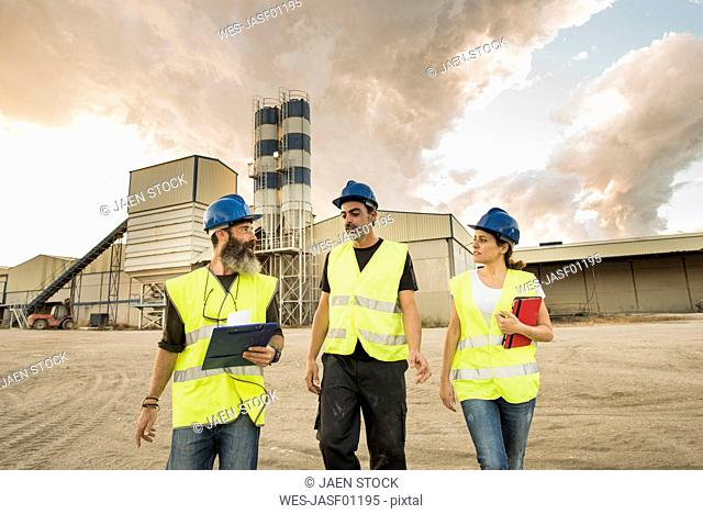 Three people in safety vests on industrial site