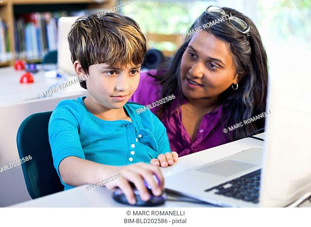Teacher helping student using laptop