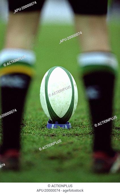 Rugby ball viewed through players legs