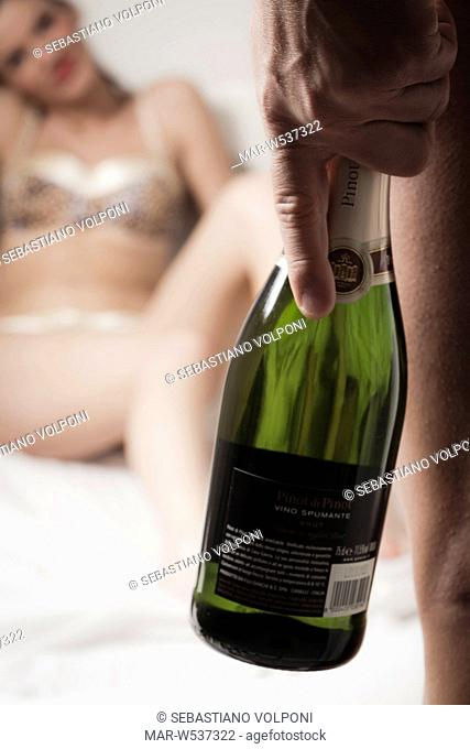 woman lying in bed, man holding bottle of spumante