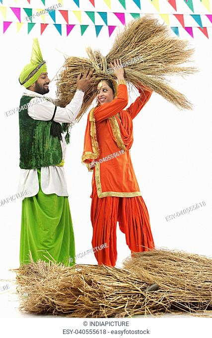 Man helping a woman carry a bale of hay