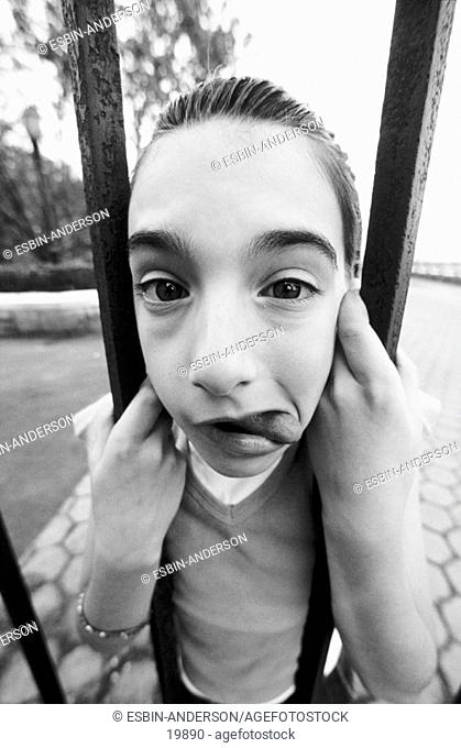 Young girl's face caught in bars