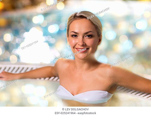 people, beauty, spa and relaxation concept - beautiful young woman wearing bikini swimsuit sitting in jacuzzi at poolside over holidays lights background