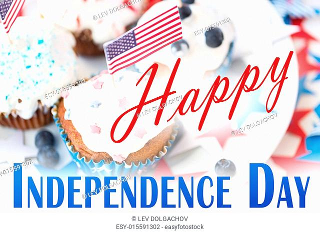 happy independence day, celebration, patriotism and holidays concept - close up of cupcakes or muffins decorated with american flags and blueberries on plate at...