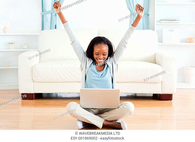 Smiling woman stretching while sitting on the floor working on her notebook