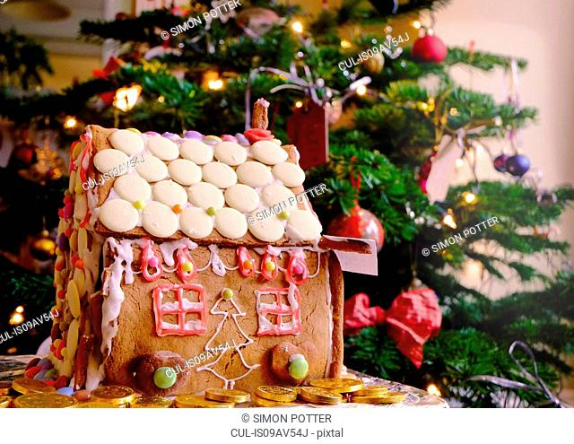 Confectionery covered gingerbread house in front of christmas tree