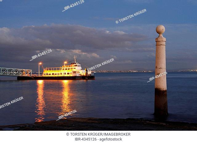 River Rio Tejo with pier and column at the Praca do Commercio at dusk, Lisbon, Portugal