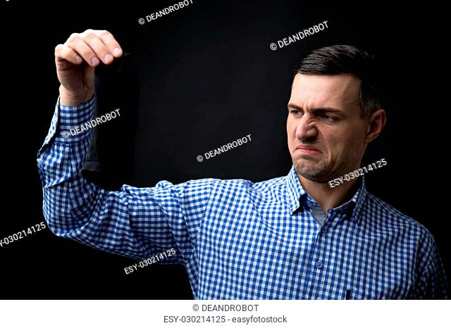 Man keeps socks over black background