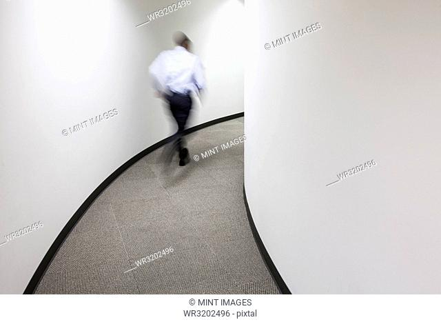 A blur of a businessman running in an office hallway