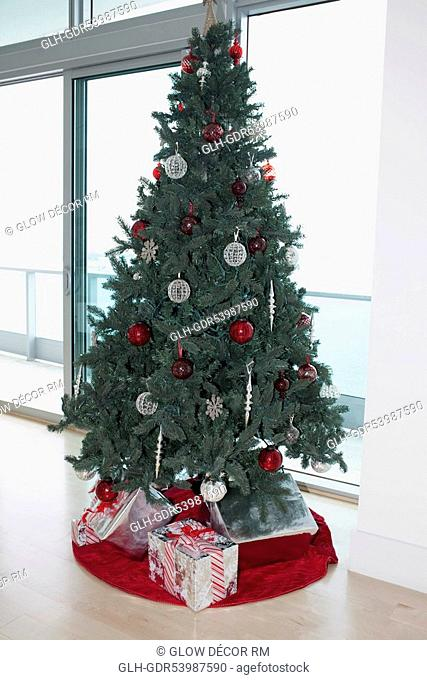 Christmas tree with gifts in a room