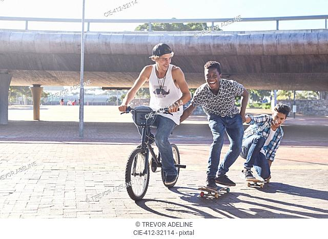 Teenage boys riding BMX bicycle and skateboarding at sunny skate park
